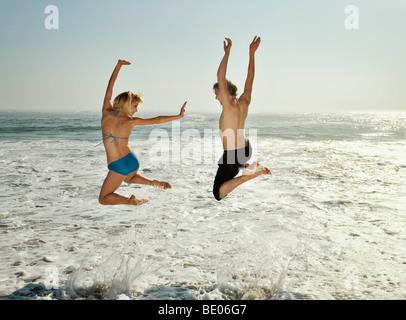 Couple sauter dans les vagues sur la plage Banque D'Images