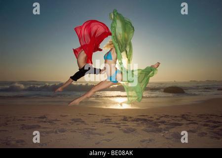 Danseurs sautant sur une plage Banque D'Images