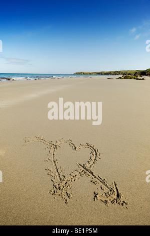 Coeur avec une flèche à travers elle tiré sur une plage de sable au Pays de Galles Banque D'Images