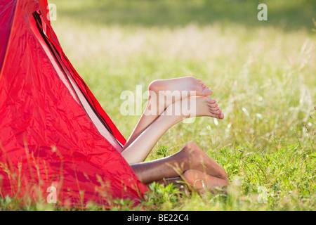 Jeune couple multiethnique située dans la tente avec les pieds croisés. Copy space Banque D'Images