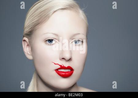 Portrait d'une jeune femme blonde avec saignements rouge à lèvres au-dessus de sa lèvre en regardant vers le spectateur, Banque D'Images