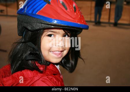 Trois ans, fille, Porter du rouge casque smiling Banque D'Images