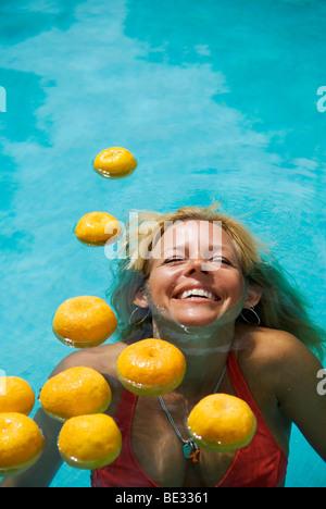 Rire belle jeune femme avec de longs cheveux blonds semi immergé dans une piscine avec des oranges flottant Banque D'Images