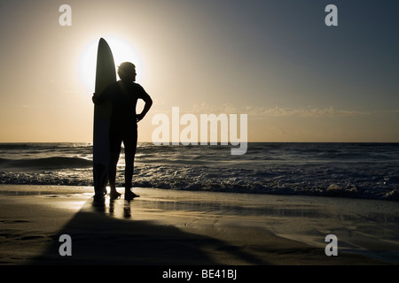 Homme debout avec une planche de surf au lever du soleil. La plage de Bondi. Sydney, New South Wales, Australia Banque D'Images