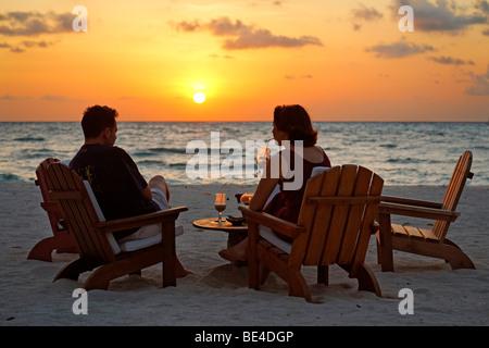 Couple assis sur des chaises à la plage avec des long drinks devant un coucher du soleil doré, Rihiveli, Island, Banque D'Images