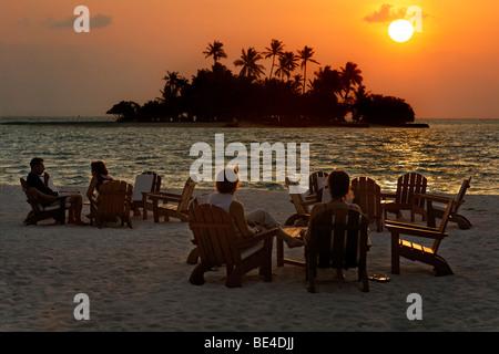 Les gens sont assis sur des chaises à la plage avec des long drinks devant un coucher du soleil d'or, les Maldives, Banque D'Images