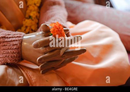 Les mains d'une statue de Sa Divine Grâce A.C. Bhaktivedanta Swami Prabhupada tenant une fleur simple.