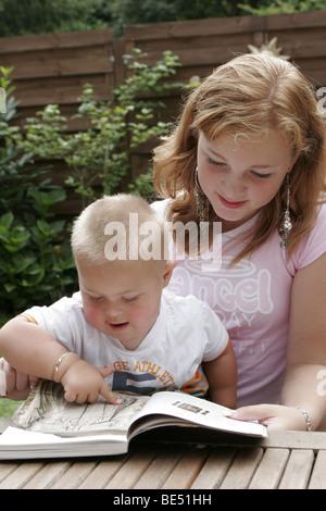 Teenage girl reading book avec syndrome de Down baby boy, pourrait être frères ou sœurs ou la garde d'un adolescent Banque D'Images