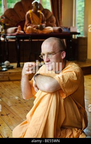 Disciple de Hare Krishna dans un temple, avec statue de Sa Divine Grâce A.C. Bhaktivedanta Swami Prabhupada derrière.