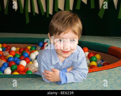 Jeune garçon, 2 ans, dans un bassin rempli de billes Banque D'Images
