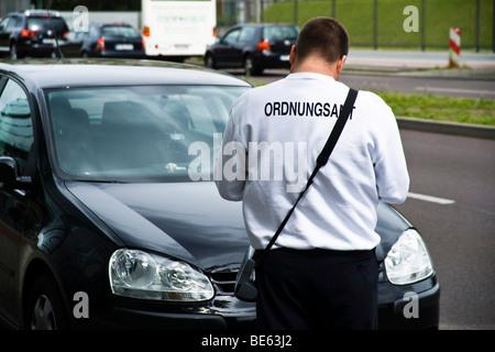 Un employé de l'office de réglementation de Berlin écrit un billet de stationnement, Berlin, Germany, Europe Banque D'Images