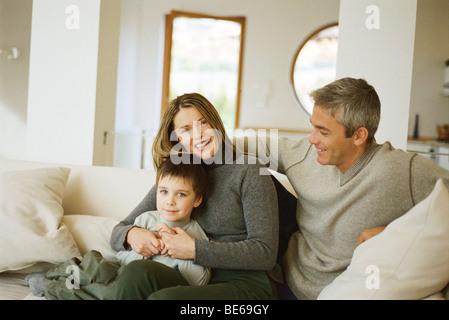 Les parents avec de jeunes assis sur son canapé, portrait Banque D'Images