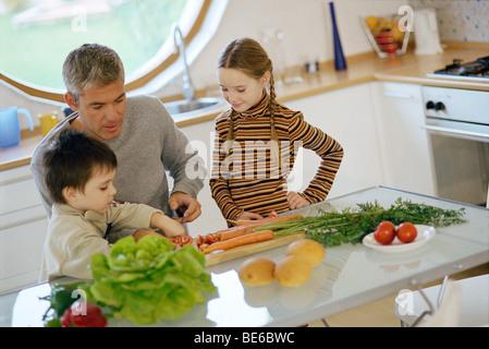 Père avec les enfants dans la cuisine, aidant les jeunes fils légumes coupés Banque D'Images
