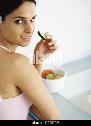 Jeune femme de manger des légumes crus en tranches Banque D'Images