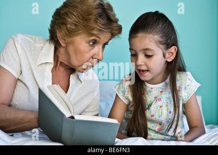 Little girl reading book avec grand-mère Banque D'Images