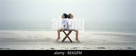 Deux garçons assis dos à dos sur chair on beach Banque D'Images