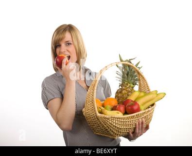 Jeune femme tenant un panier de fruits et de mordre dans une pomme rouge Banque D'Images