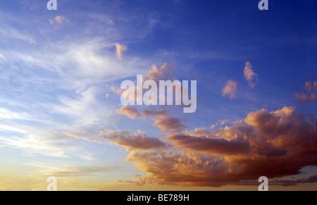 Ciel bleu au coucher du soleil, avec des nuages blancs et orange Banque D'Images