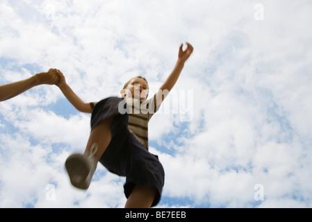 Boy holding mains adultes, sauter dans les airs, low angle view