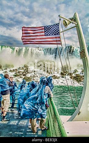 Les touristes en bleu se parcs très humide dans l'eau et du vent sur le Maid of the Mist boat célèbre Rainbow Falls Banque D'Images