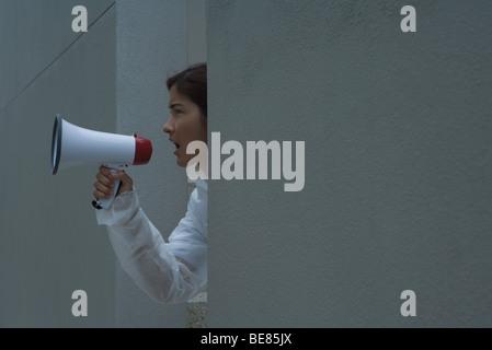 Femme de crier dans un mégaphone, side view