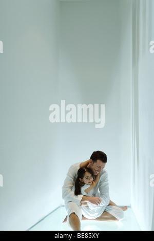 Petite fille sur les genoux du père, smiling over Shoulder at camera Banque D'Images
