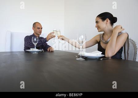Couple assis à table, tintement des verres de champagne Banque D'Images