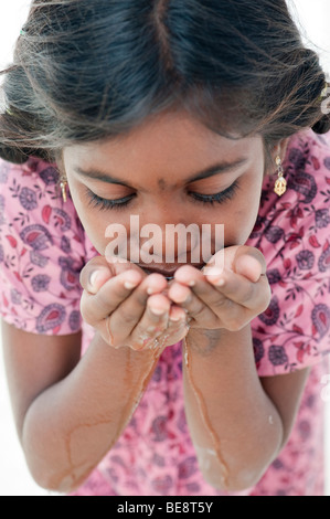 Indian girl with creux des mains de l'eau potable. L'Inde Banque D'Images