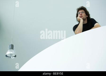 Jeune homme sur le balcon, se penchant sur le coude, low angle view