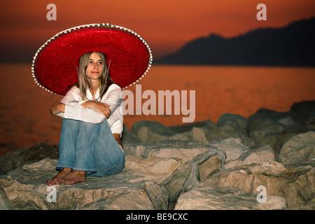Jeune fille avec un sombrero assis par le coucher du soleil Banque D'Images