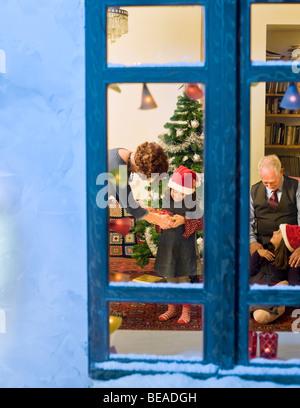 Les grands-parents de donner cadeau de Noël à leurs petites-filles Banque D'Images