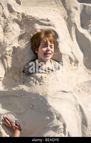 Un jeune garçon enterré dans le sable, Cable Beach, Nassau, Bahamas, Caraïbes Banque D'Images