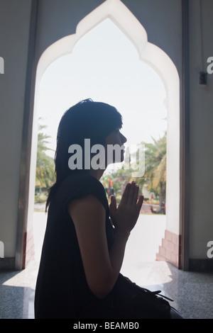 Asian woman praying in temple
