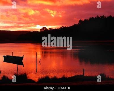 Coucher du soleil dans le lac avec un bateau d'ossature Banque D'Images
