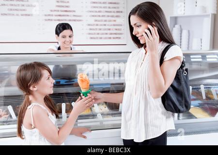 Femme donnant à sa fille de la crème glacée et de parler sur un téléphone mobile Banque D'Images