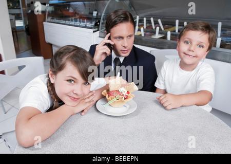 Homme avec ses deux enfants dans un glacier Banque D'Images