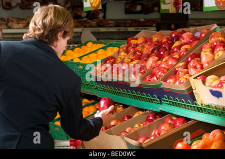 L'homme tenant une pomme dans un supermarché Banque D'Images