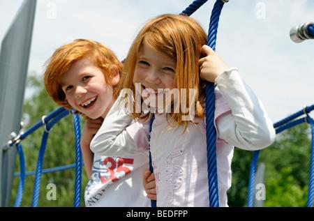 Enfants jouant sur un jeu extérieur sur une aire de jeux Banque D'Images