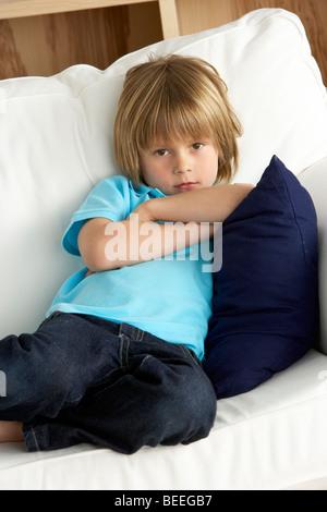 Jeune garçon assis sur un canapé à la maison Banque D'Images