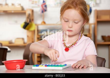 Jeune garçon jouant au préscolaire/Montessori Banque D'Images