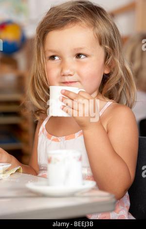 Jeune garçon prenant le thé au préscolaire/Montessori Banque D'Images