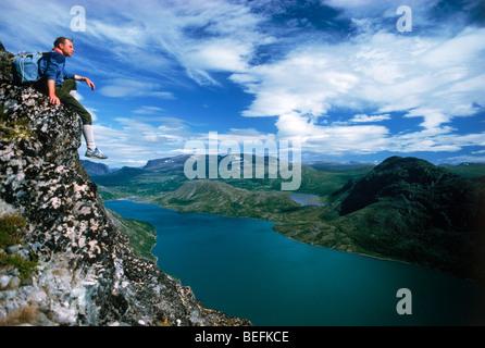 Assis au-dessus de Gjende randonneur (ou Gjendin) Lac dans les montagnes de Jotunheimen dans le parc national de Banque D'Images