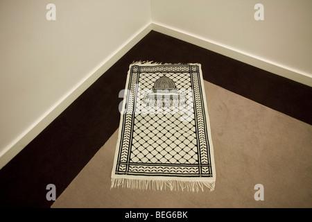 Un tapis de prière islamique positionné vers l'Est de la Mecque, dans un coin de la salle multi-foi à Heathrow T5. Banque D'Images