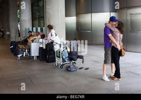 Les jeunes amoureux embrasser dans station de bus à arrivées après longue absence aprt à Heathrow Terminal 5. Banque D'Images