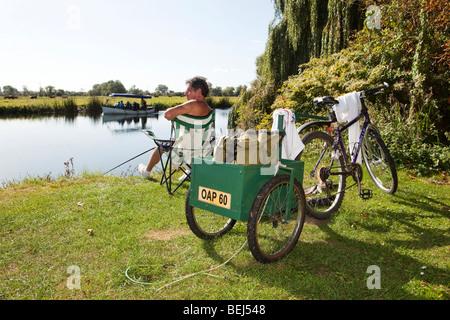 L'Angleterre, Cambridgeshire, Huntingdon, Hartford, pensionné avec remorque à vélo la pêche en rivière Great Ouse Banque D'Images