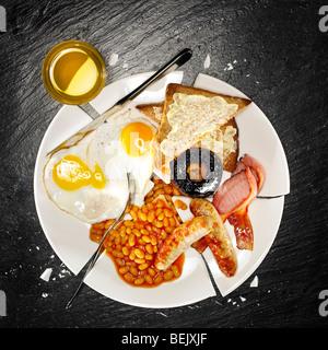 Un petit-déjeuner complet contenant des œufs, saucisses, bacon, fèves au lard, champignons et pain grillé