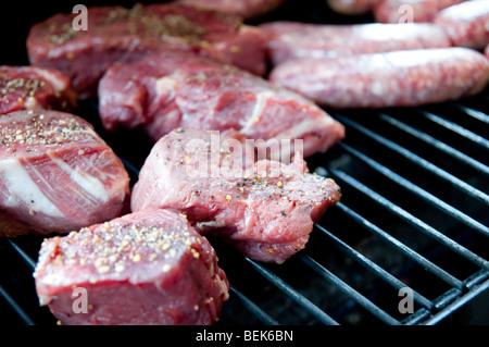 Steak cru assaisonné les côtelettes et les saucisses sur une grille de barbecue Banque D'Images