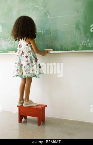 Little Girl standing on stool in front of blackboard, rear view