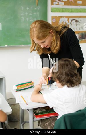 Élève d'école élémentaire l'enseignant montrant comment dessiner à l'aide de boussole Banque D'Images