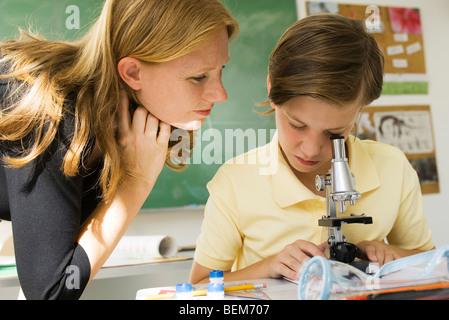 Boy looking through microscope, l'observation de l'enseignant